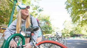 A student working on her bike on campus